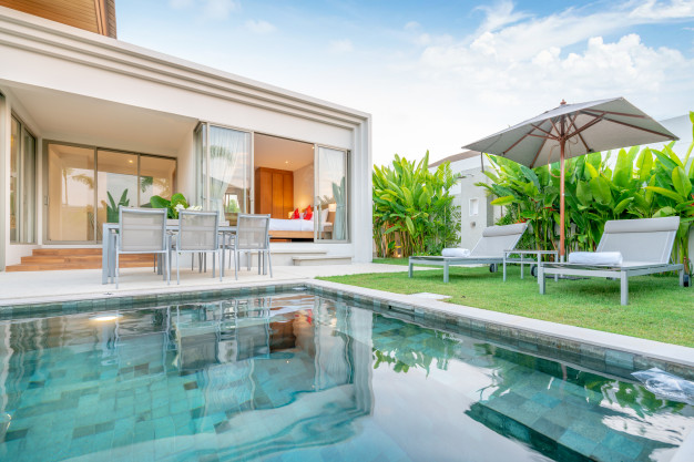 home-house-exterior-design-showing-tropical-pool-villa-with-greenery-garden-sun-bed-umbrella-pool-towels_41487-361