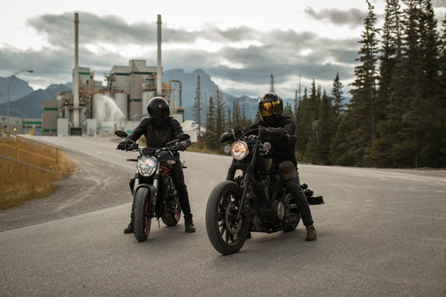 Dvaja motorkári v čiernych overaloch stoja na ceste