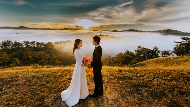 Ženích a nevesta stoja na kopci a držia sa za ruky.jpg