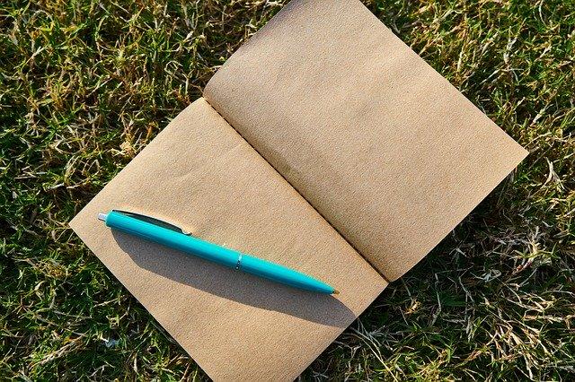 Zápisník s hnedými listami a pero v tráve